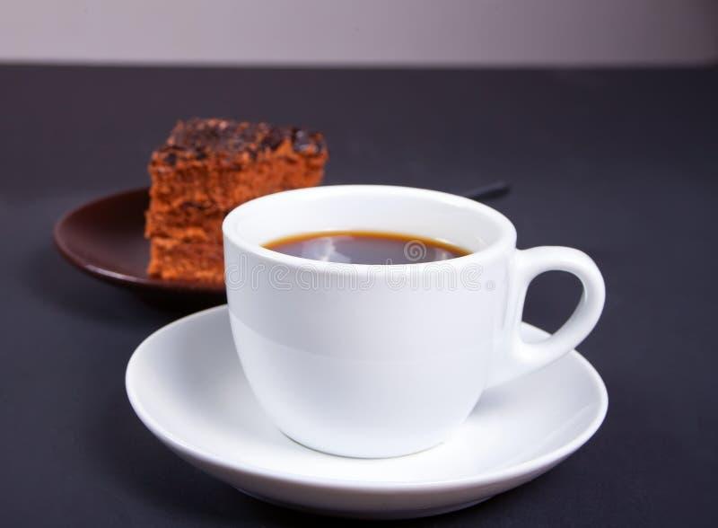Tasse Kaffee mit köstlichem Stück des Schokoladenkuchens auf der schwarzen Tabelle stockbilder