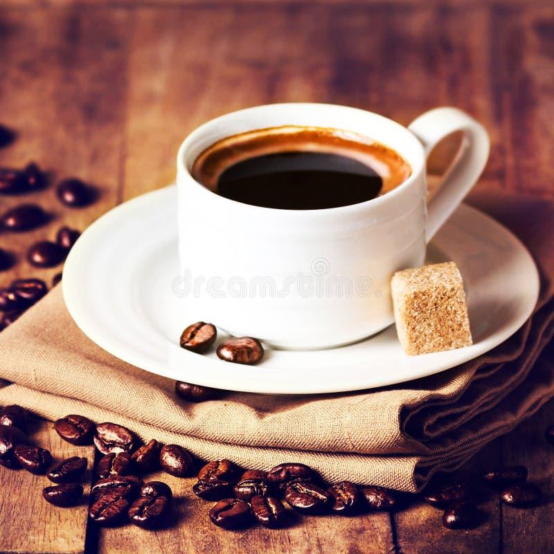 Tasse Kaffee mit Kaffeebohnen auf Holztisch auf braunem backgro lizenzfreies stockfoto