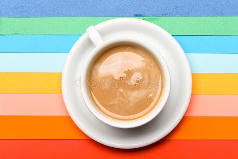 Tasse Kaffee mit Milch- oder Cappuccinogetränk auf buntem als Regenbogenhintergrund Dosis des Energiekonzeptes Kaffee an lizenzfreie stockbilder