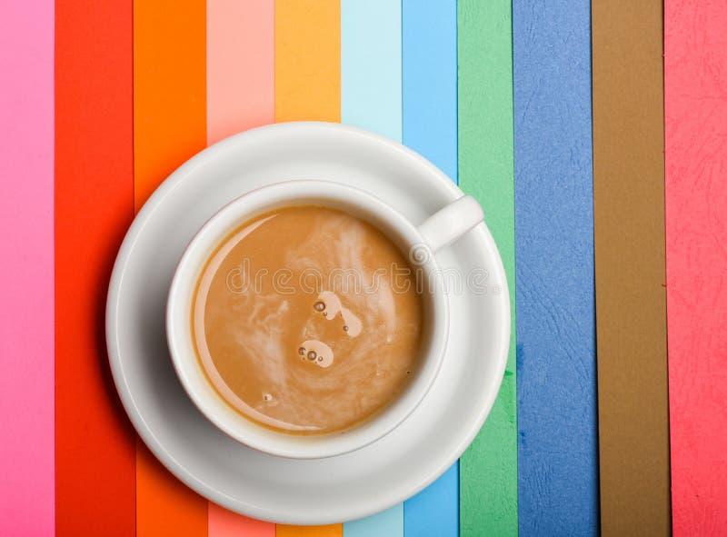 Tasse Kaffee mit Milch- oder Cappuccinogetränk auf buntem als Regenbogenhintergrund Dosis des Energiekonzeptes Getränk mit lizenzfreie stockfotografie