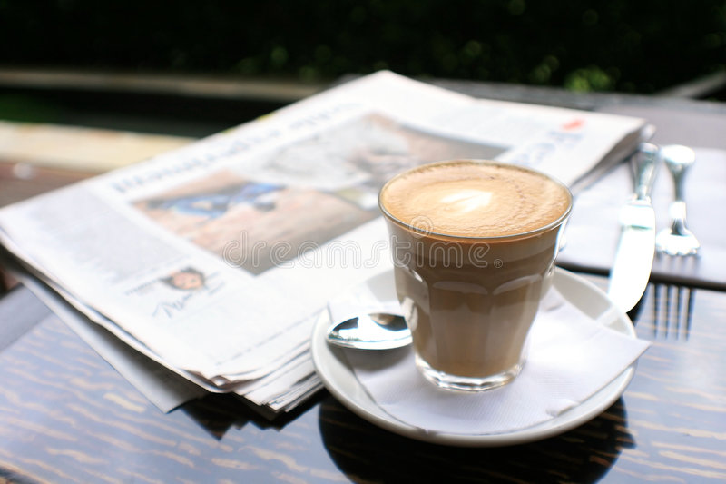 Tasse Kaffee mit Nachrichtenpapier auf Tabelle stockfotos