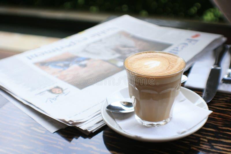 Tasse Kaffee mit Nachrichtenpapier auf Tabelle stockfotografie