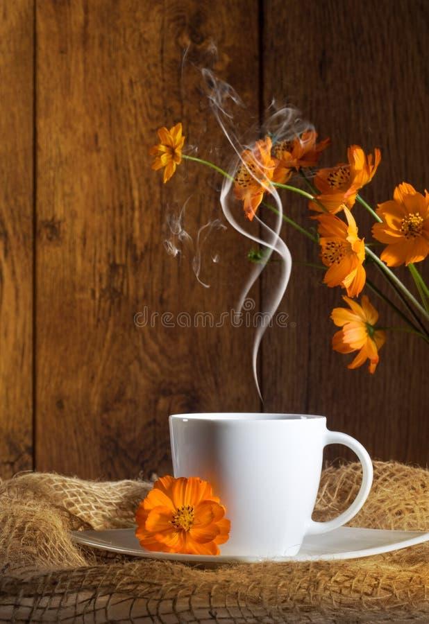 Tasse Kaffee mit orange Blumen lizenzfreie stockbilder