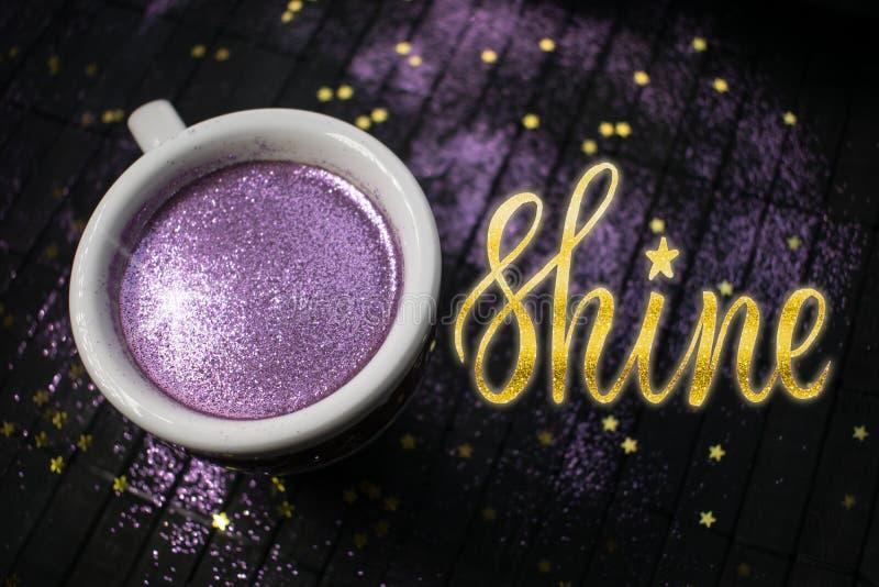 Tasse Kaffee mit purpurrotem Funkeln auf dunklem Hintergrund mit Goldenem lizenzfreies stockbild
