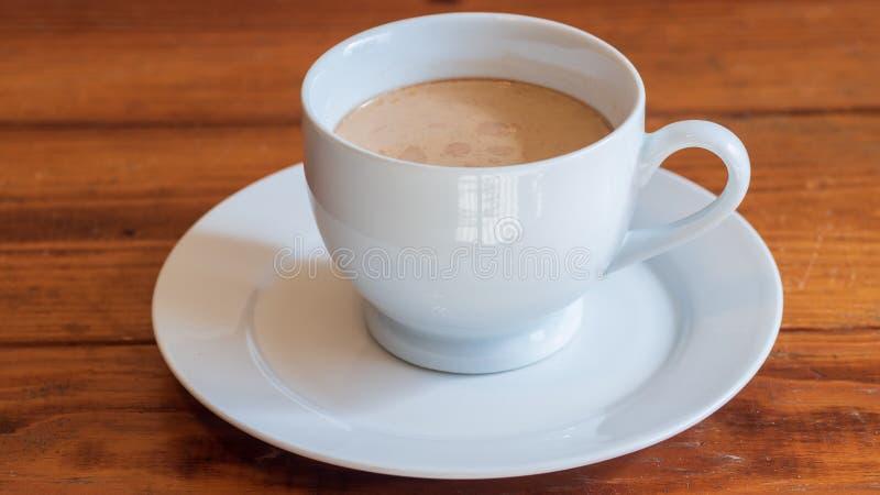 Tasse Kaffee mit Sahne in der weißen keramischen Schale, auf kleiner weißer keramischer Platte, auf Holzoberfläche stockfotografie