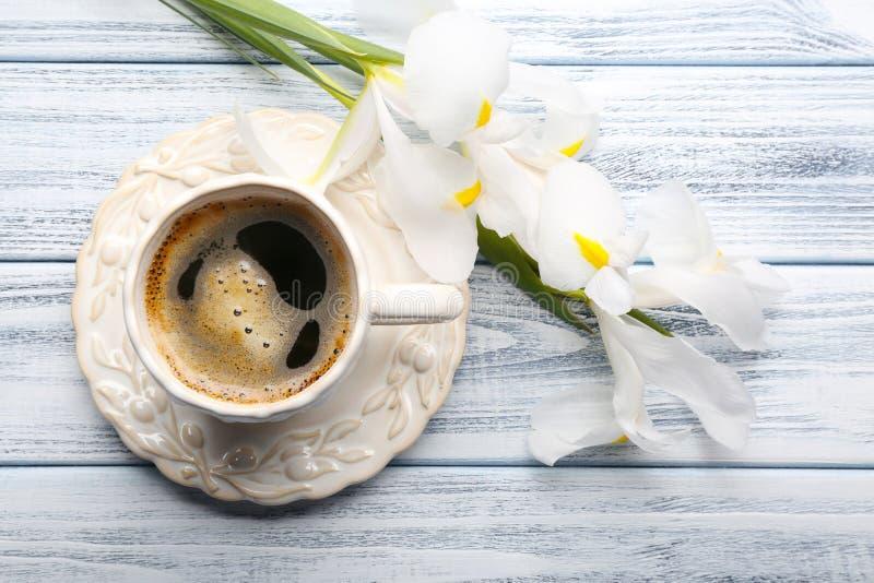 Tasse Kaffee mit schönen Blumen auf hölzernem Hintergrund lizenzfreie stockfotografie