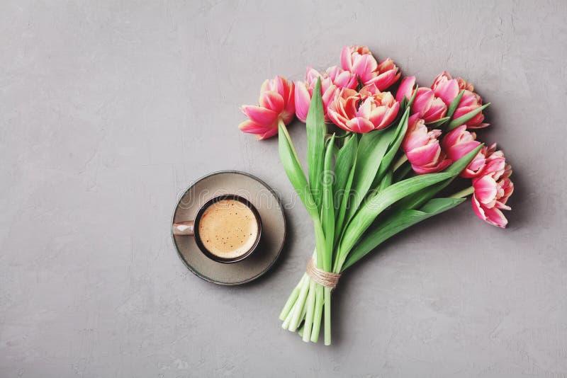 Tasse Kaffee mit schönen rosa Blumen für guten Morgen auf grauer Steintischplatteansicht in Ebene legen Art Frühstück am Mutterta lizenzfreies stockfoto