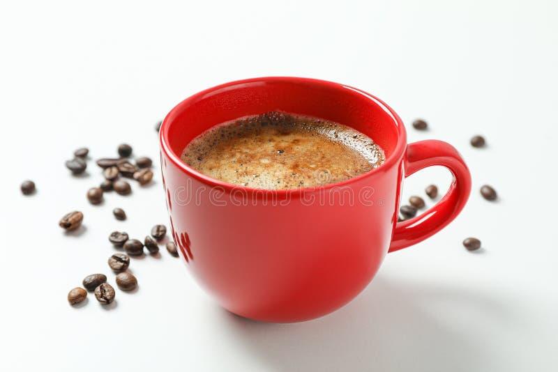 Tasse Kaffee mit schaumigem Schaum und Kaffeebohnen auf weißem Hintergrund, Raum für Text und Nahaufnahme stockfotografie