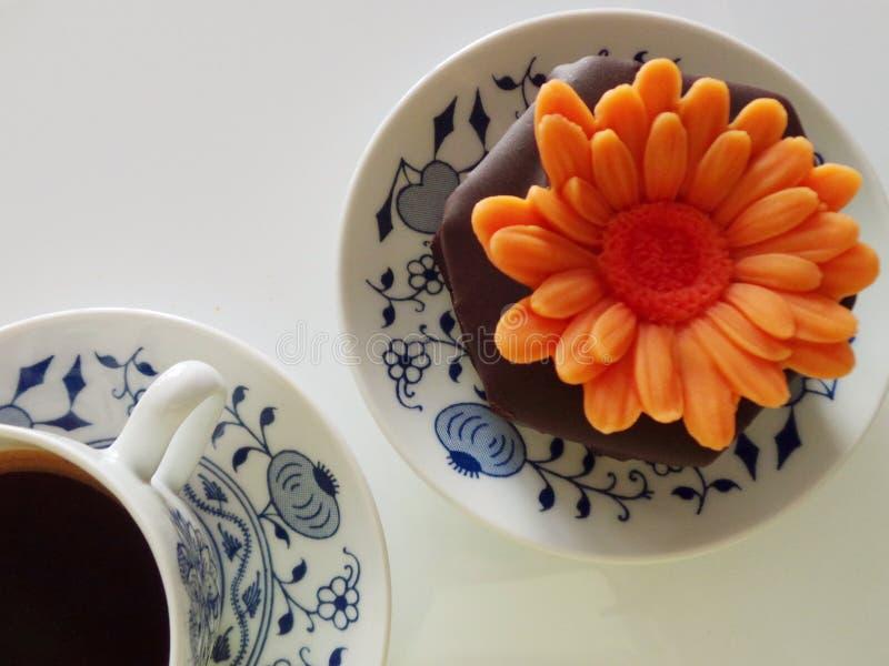 Tasse Kaffee mit Schokoladenmuffin und orange Blumenstillleben lizenzfreie stockfotos