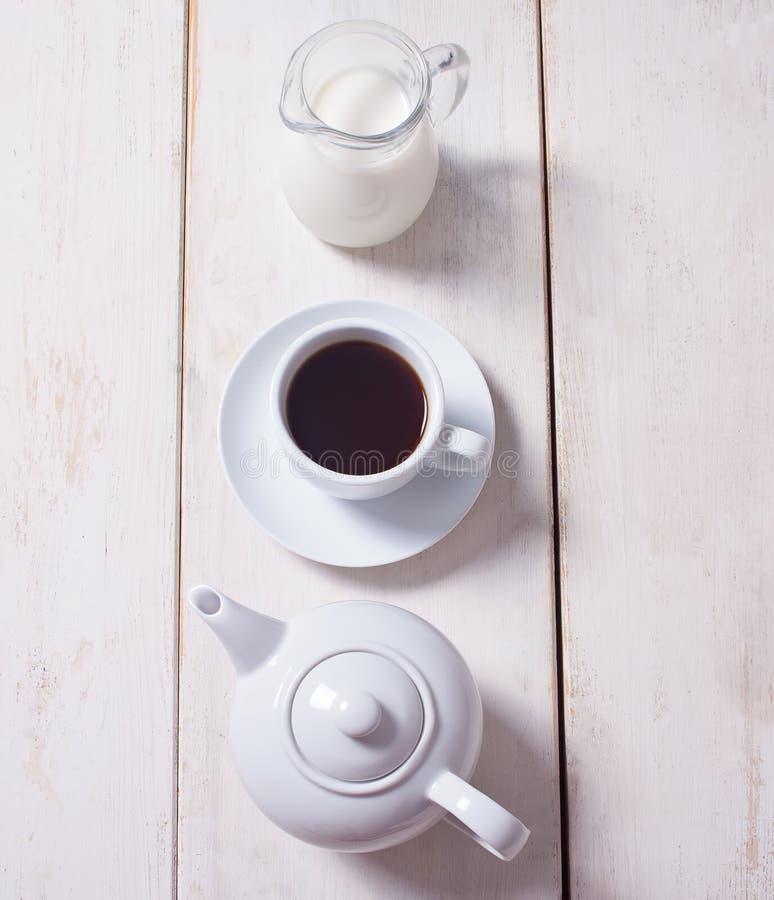 Tasse Kaffee, Teekanne und Krug mit Milch in der Reihe über weißem hölzernem Hintergrund Flache Lage, Kopienraum lizenzfreies stockbild