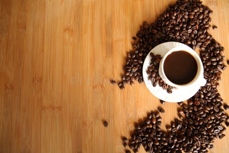 Tasse Kaffee- und Auslesebohnen auf Holztisch stockbilder
