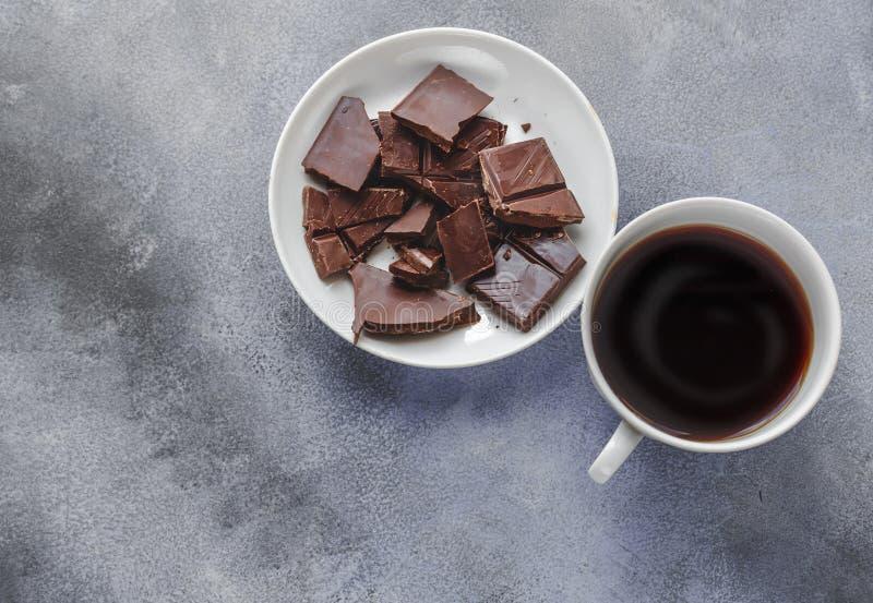 Tasse Kaffee und dunkle Schokolade auf weißer Platte auf grauem Hintergrund, Draufsicht lizenzfreie stockfotos
