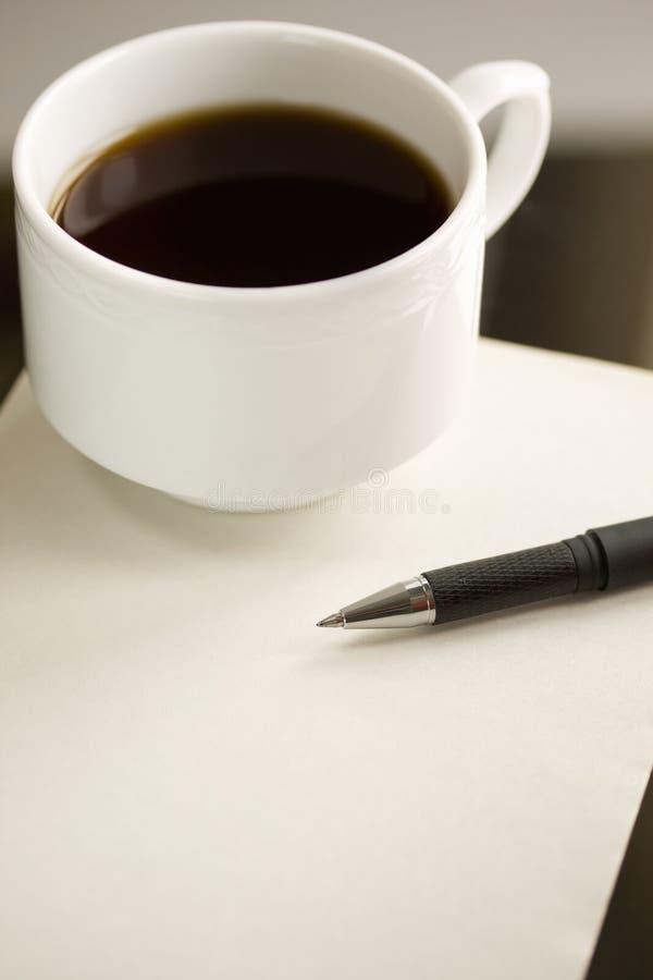 Tasse Kaffee und Feder auf dem Papier. stockbilder