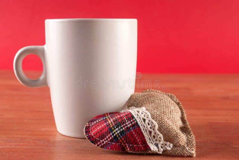 Tasse Kaffee und Herd auf hölzernem Schreibtisch und rotem Hintergrund stockfotos