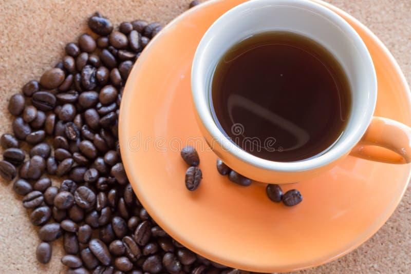 Tasse Kaffee und Kaffeebohnen auf braunem Gewebepapier stockfoto