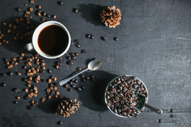 Tasse Kaffee und Kaffeebohnen auf einem schwarzen Hintergrund lizenzfreie stockfotografie