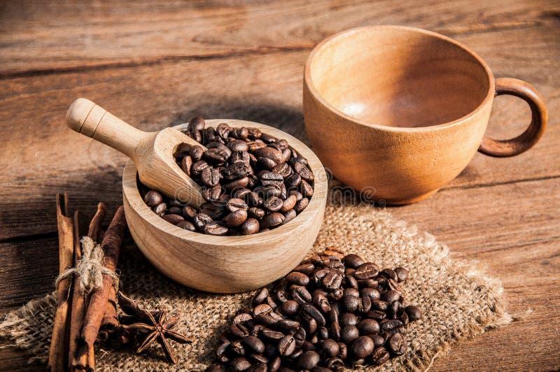Tasse Kaffee und Kaffeebohnen auf Holztisch lizenzfreie stockbilder