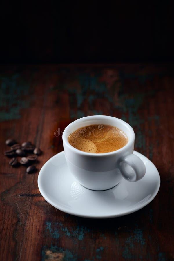 Tasse Kaffee und Kaffeebohnen auf rustikalem h?lzernem Hintergrund lizenzfreies stockfoto