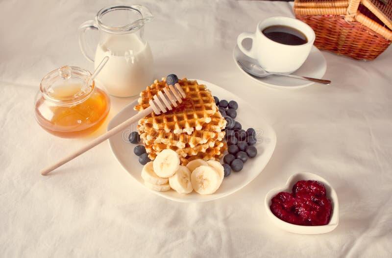Tasse Kaffee und Waffeln mit Bananen, Stau, Blaubeeren und Honig lizenzfreie stockfotos