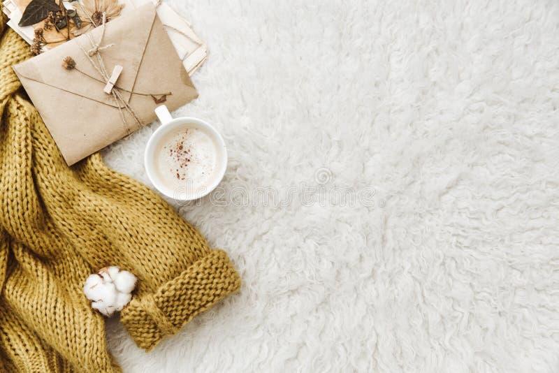 Tasse Kaffee, warme Strickjacke und Umschlag Flache Lagezusammensetzung lizenzfreies stockfoto