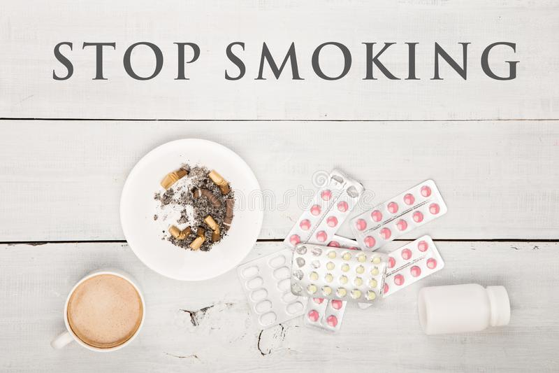 Tasse Kaffee, Zigaretten, medizinische Flaschen und Pillen und Text hören auf zu rauchen lizenzfreies stockfoto