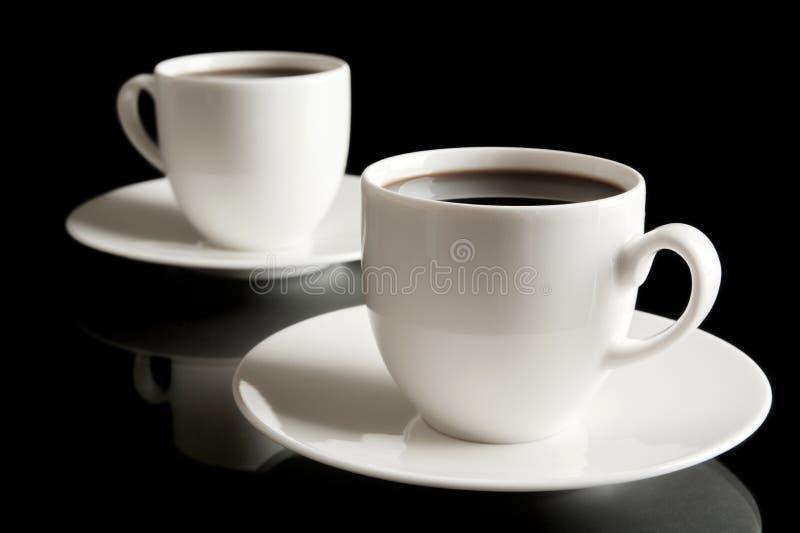 Tasse Kaffees mit der Untertasse lokalisiert auf Schwarzem lizenzfreies stockfoto