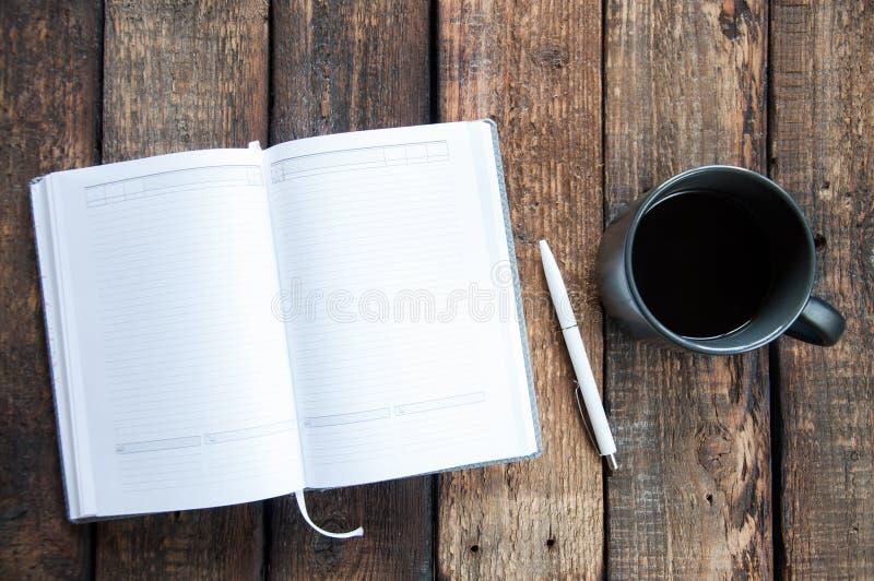 Tasse noire avec du café et le bloc-notes ouvert sur une table en bois Fond en bois de Brown panneau photographie stock libre de droits