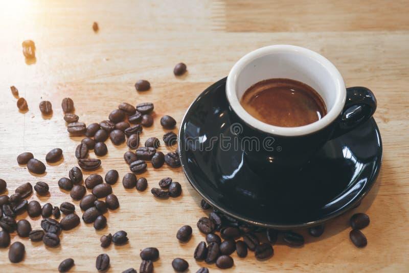 Tasse noire d'expresso avec les grains de café renversés sur la table en bois photo libre de droits