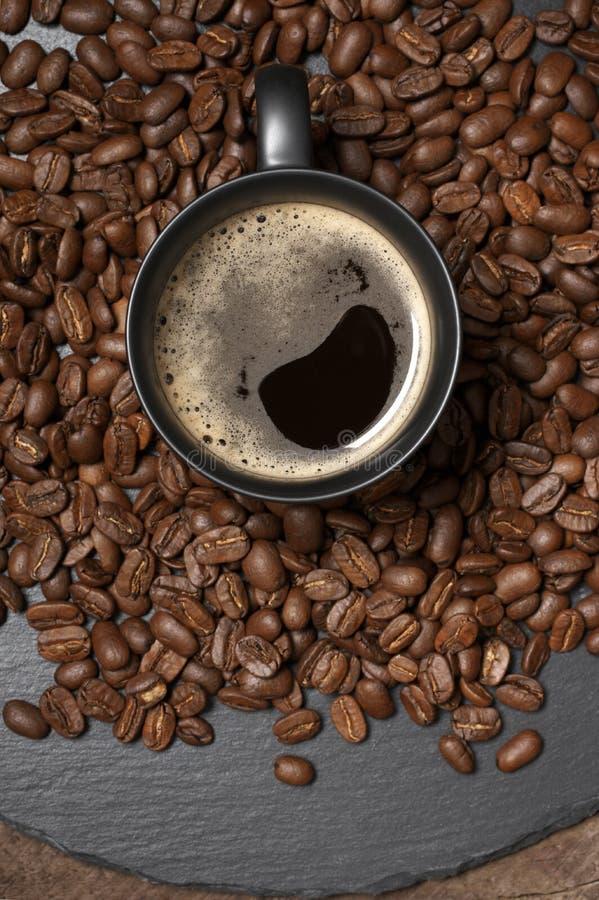 Tasse noire de café chaud en grains de café photos stock
