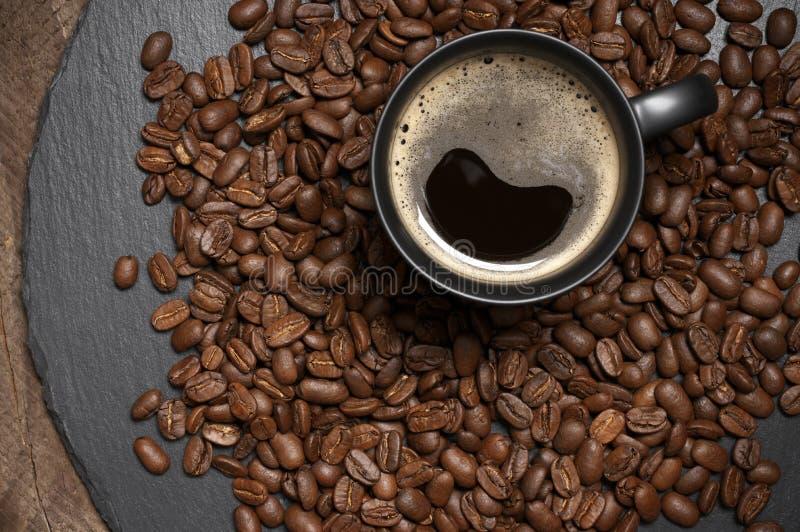 Tasse noire de café chaud en grains de café photographie stock