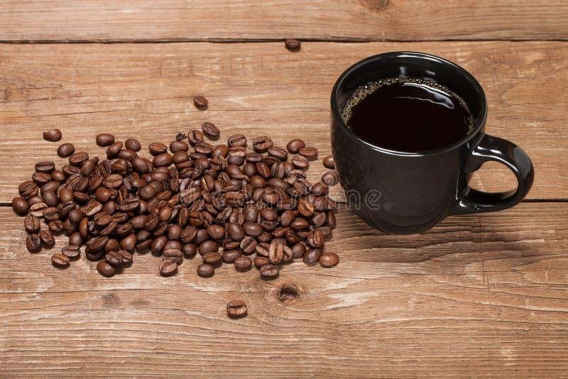 Tasse noire de café et de graines de café sur la vieille table en bois photographie stock