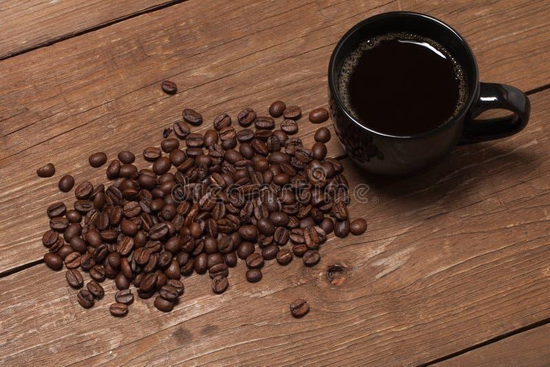 Tasse noire de café et de graines de café sur la vieille table en bois image libre de droits