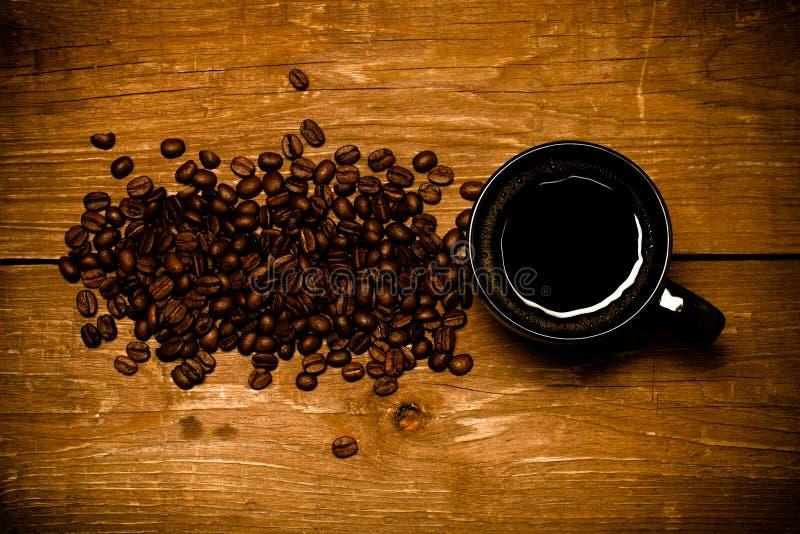 Tasse noire de café et de graines de café sur la vieille table en bois toned photo libre de droits