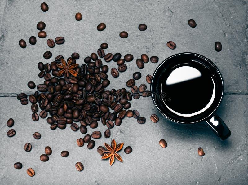 Tasse noire de café et de graines de café sur le fond d'ardoise À photos stock