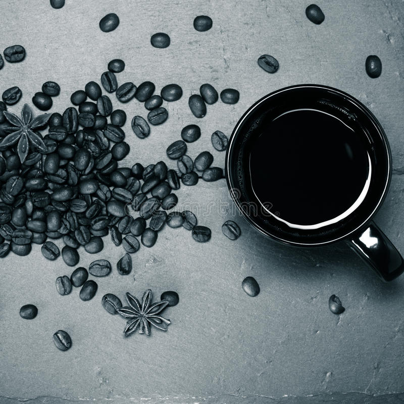 Tasse noire de café et de graines de café sur le fond d'ardoise À images libres de droits
