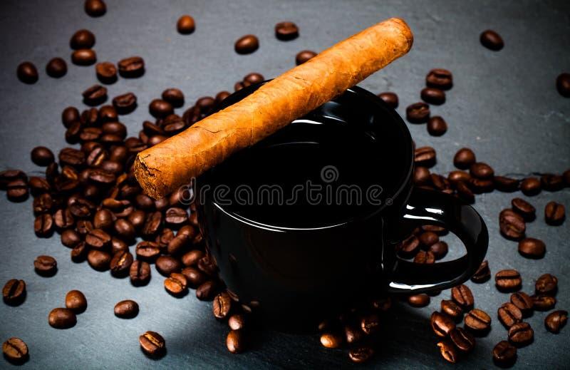Tasse noire de graines de café, de cigare et de café sur le backgro d'ardoise image libre de droits