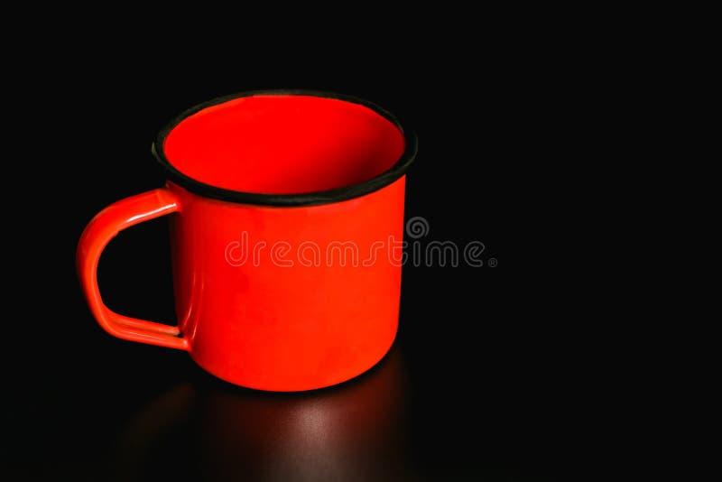 Tasse orange d'émail sur un fond noir photos stock