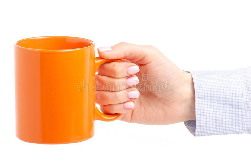 Tasse orange de tasse dans la main femelle image stock