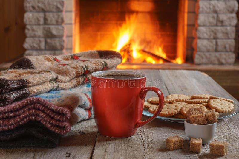 Tasse orange pour le thé ou le café ; les choses de laine s'approchent de la cheminée confortable image stock