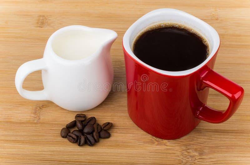 Tasse rouge avec l'expresso, les grains de café et la cruche de lait images stock