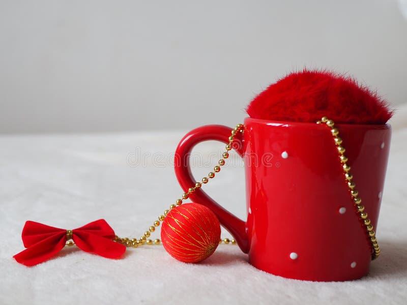Tasse rouge avec la couverture, la babiole et l'arc pelucheux Fin vers le haut photos stock
