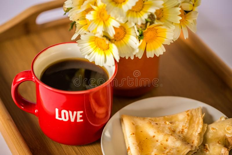 """Tasse rouge avec le mot """"amour """"avec du café/thé chaud, un bouquet des marguerites et des crêpes avec du miel sur un plateau en b photo libre de droits"""