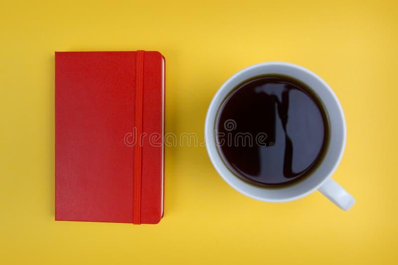 Tasse rouge de carnet et de café sur le fond jaune lumineux images libres de droits