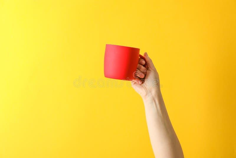 Tasse rouge de prise femelle de main sur le fond de couleur photo stock