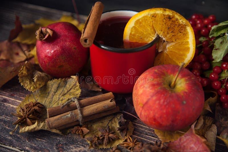 Tasse rouge de vin chaud chaud en automne parmi des feuilles images stock