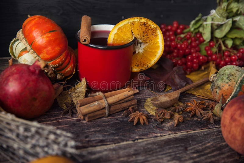 Tasse rouge de vin chaud chaud en automne parmi des feuilles image stock