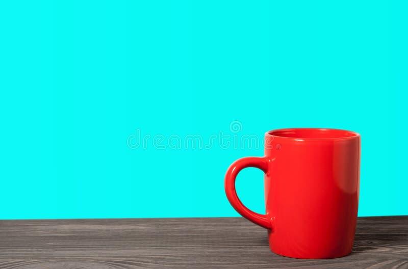 Tasse rouge sur une surface en bois sur le bleu photographie stock libre de droits