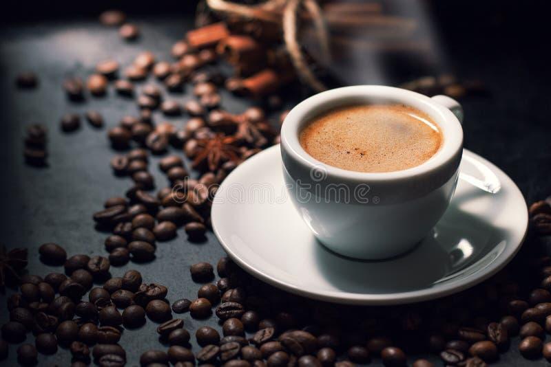 Tasse savoureuse fraîche d'expresso de café chaud avec des grains de café sur l'obscurité photo stock