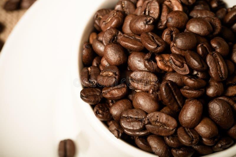 Tasse, soucoupe et grains de café sur un fond de toile de jute Département peu profond photo stock