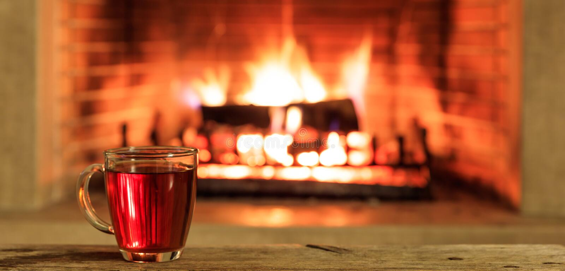 Tasse Tee auf einem brennenden Kaminhintergrund lizenzfreies stockfoto